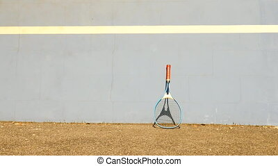 Bouncing Tennis Ball against Wall. Tennis ball jumping on the court, very old aluminnum tennis racket lean against the wall.