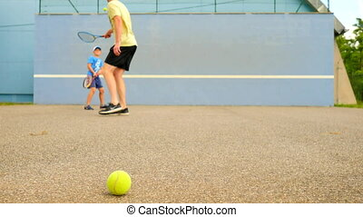 Father and son practice tennis at training wall. Hobby...