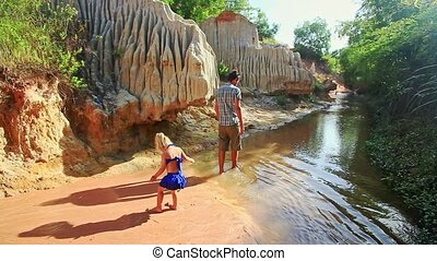 Little Girl Plays on Wet Sand Walks with Dad along Stream -...