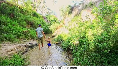 Dad with Daughter Walk Barefoot along Pure Narrow Stream -...
