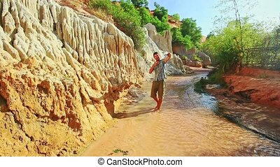 Man Makes Selfie against Large Yellow Rock on Fairy Stream