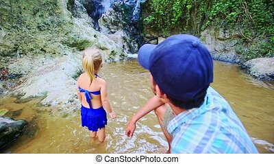 Father and Daughter Stand in Stream Look at Waterfall -...