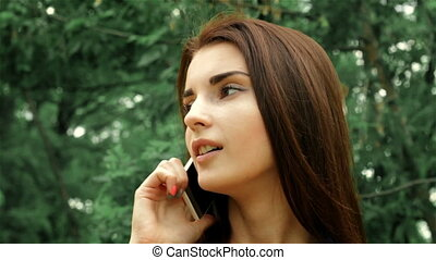 a charming girl is standing on the street and talking on the phone