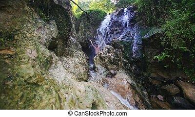 Closeup Man Bathes under Waterfall Jets among Rocks -...