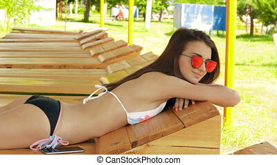 Sexy brunette teen in swimsuit and sunglasses tans in the...