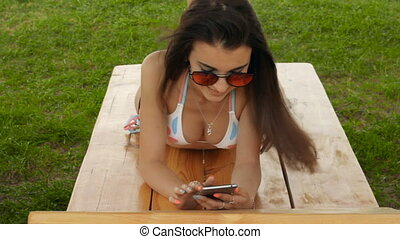 glamour girl in a bathing suit and glasses tans and looking...