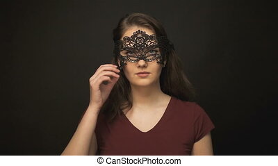 Brunette woman undressing lace mask on dark background