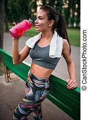 Woman drink water from sport bottle - Sporty woman drink...