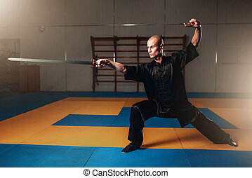 Wushu master training with sword, martial arts. Man in black...