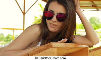 beautiful young women in bright pink glasses lying on the...