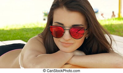 beautiful smiling brunette in glasses on the beach sunning bright