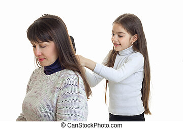 little daughter Combs her hair her mother close-up isolated...