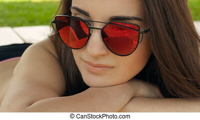 attractive young girl in mirror glasses lay on the beach,...