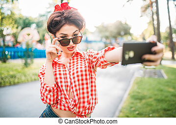 Pinup sexy lady makes selfie on camera in park - Pinup sexy...