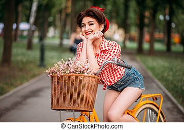 Pinup woman on bicycle with backet of flowers, vintage...