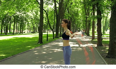 slim girl in the Park and jumps rope - Athletic slim girl...