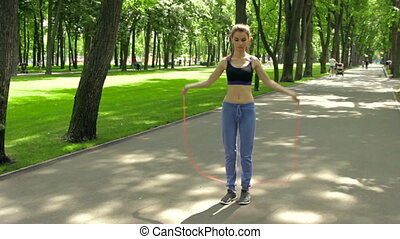 a young energetic girl jumping rope in the summer