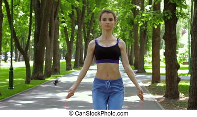 Athletic slim girl jumping rope in the Park
