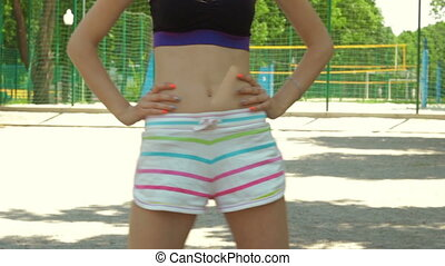 young girl with slender bulge in shorts doing exercises on the streets