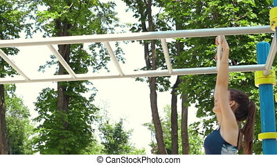 young woman moves with hands on the ladder - athletic young...