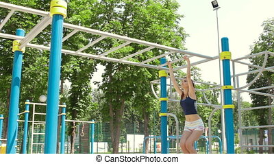 athletic Lady moves with her hands on the ladder in a park...