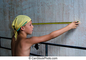 teenager measuring a wall