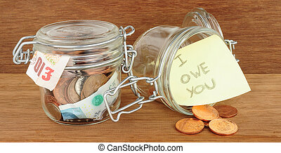 Glass jars filled with cash savings on a wood background