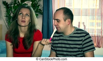 Frustrated wife and husband with negative pregnancy test in...