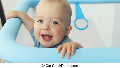 Baby boy smiling at camera while standing manege - Adorable...
