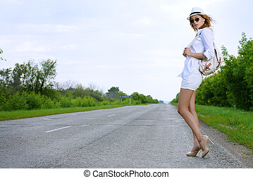 hitch-hike by the road - Hitchhiking girl. Attractive young...
