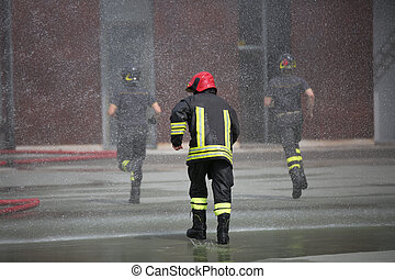 Firefighters under the splashes of water - Firefighters run...