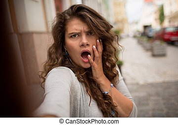 Young woman showing disturbance face on selfie shot.