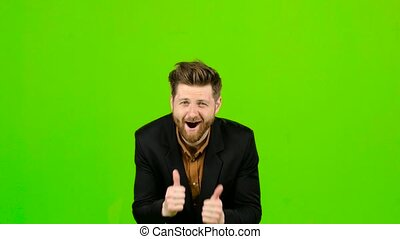 Guy businessman shows thumbs up on both hands. Green screen...