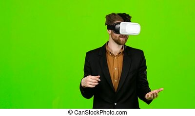 Businessman in virtual reality is having fun and smiling....