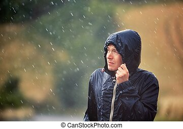 Man with dog in heavy rain - Young man walking in nature...