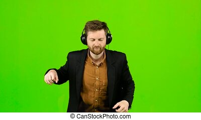 Guy listens to music in headphones and dances. Green screen...