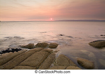 Pink sunset light on a coastal scene