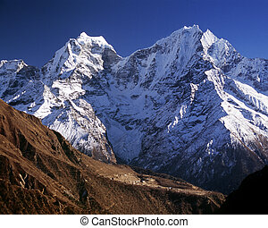 Giant mountains in the Himalaya dwarf a tiny village