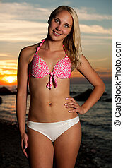 Young woman on the beach at sunset on a hot summer day