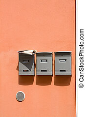 Three mailboxes - Three mail boxes with newspapers on a...