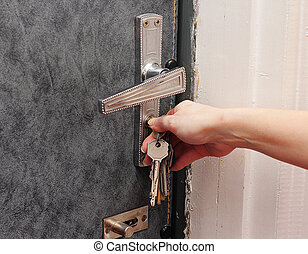 Female hand opens the door with a key.