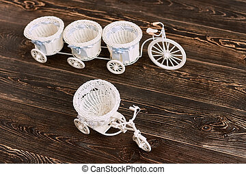 Tricycle flower baskets on wood. White plastic toys. Cheap...