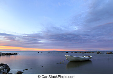 White boat in sea at sunset
