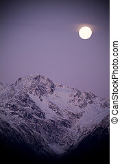 Moon rises over snow capped mountains at twilight