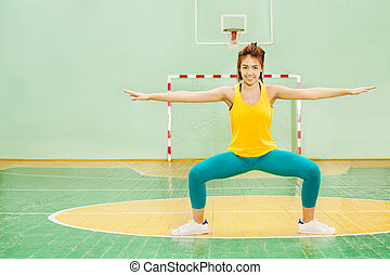 Asian girl performing sumo squat in sports hall - Portrait...