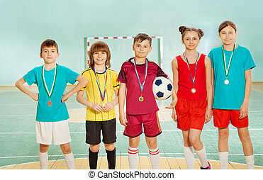 Football winners standing in line with medals - Group of...