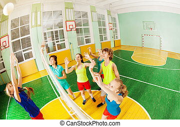 Teenagers playing volleyball in sports hall