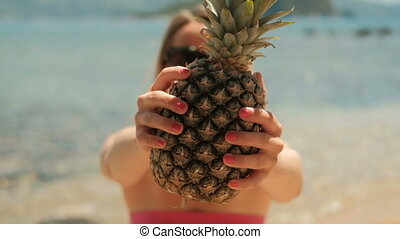 Young woman holding pineapple standing on beach in summer....