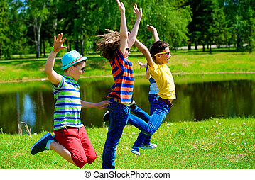 carefree childlike joy - Group of cheerful children jumping...