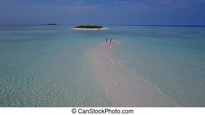 v04020 Aerial flying drone view of Maldives white sandy beach 2 people young couple man woman romantic love on sunny tropical paradise island with aqua blue sky sea water ocean 4k
